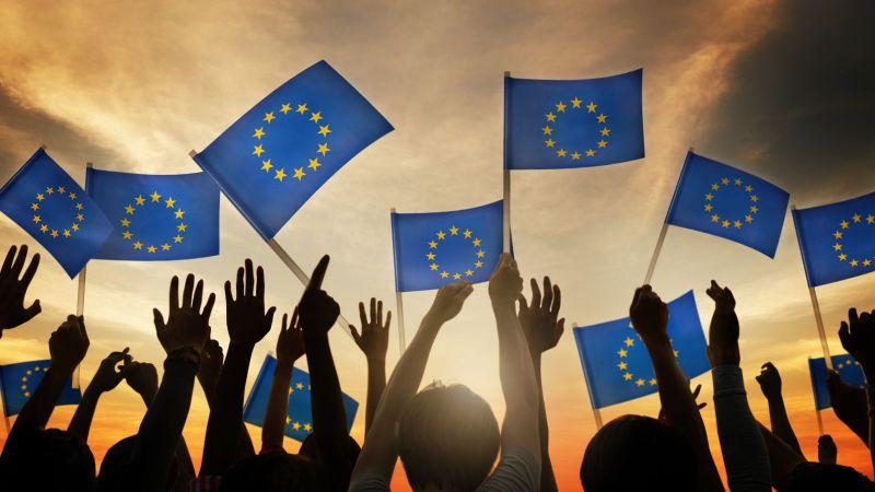 Das Bild zeigt eine Menschengruppe, d ihre Arme heben und europäische Flaggen halten. Im Hintergrund ist die untergehende Sonne zu sehen.