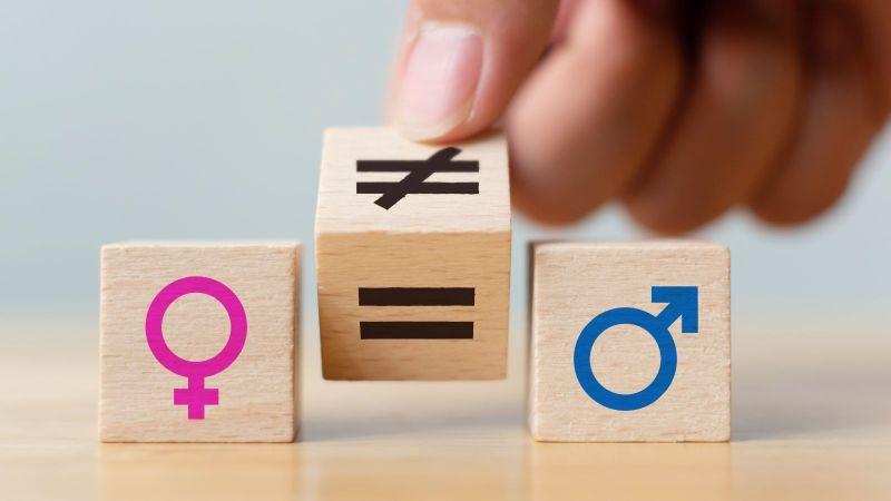 """Das Bild zeigt 3 Holzwürfel. Auf dem linken Würfel ist das Symbol """"weiblich"""" und auf dem rechten das Symbol """"männlich"""" abgebildet. Eine Hand dreht den mittleren Würfel von einem """"Ungleich-"""" auf ein """"Gleichheitszeichen""""."""