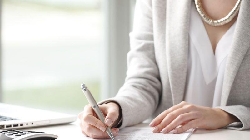 Das Bild zeigt einen Schreibtisch mit Laptop und Taschenrechner, an dem eine Frau ein Formular mit einem Stift ausfüllt.