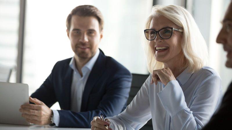 Eine Dame und ein Herr in Business Kleidung, die den Betrachter ansehen