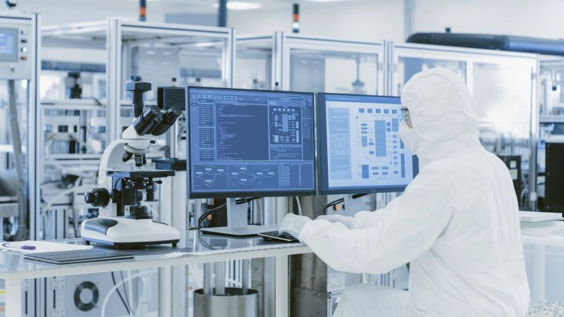 Person in weißer Schutzkleidung sitzt in einem Labor vor Computerbildschirmen und bedient eine Tastatur.
