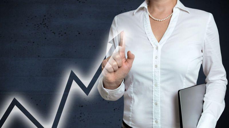 Das Bild zeigt eine ansteigende Kurve, die von einer Unternehmerin am ansteigenden Pfeil berührt wird.