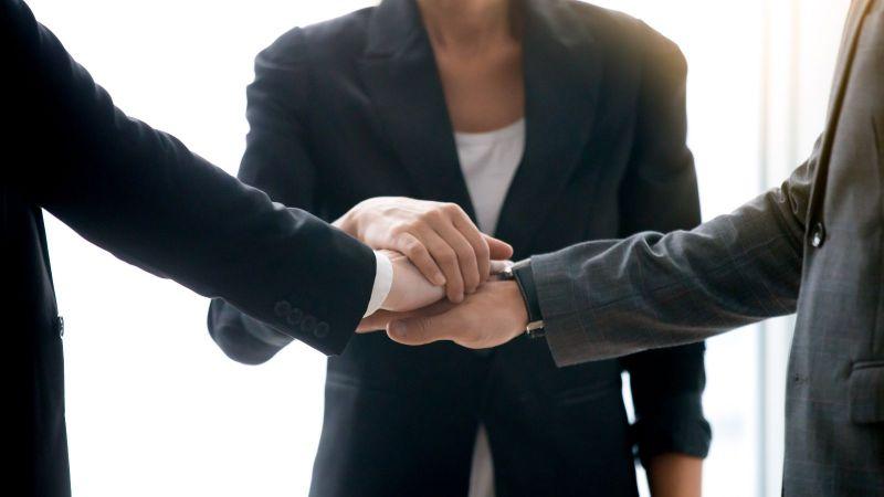 Das Bild zeigt drei Personen in Businesskleidung, die sich die Hände reichen.