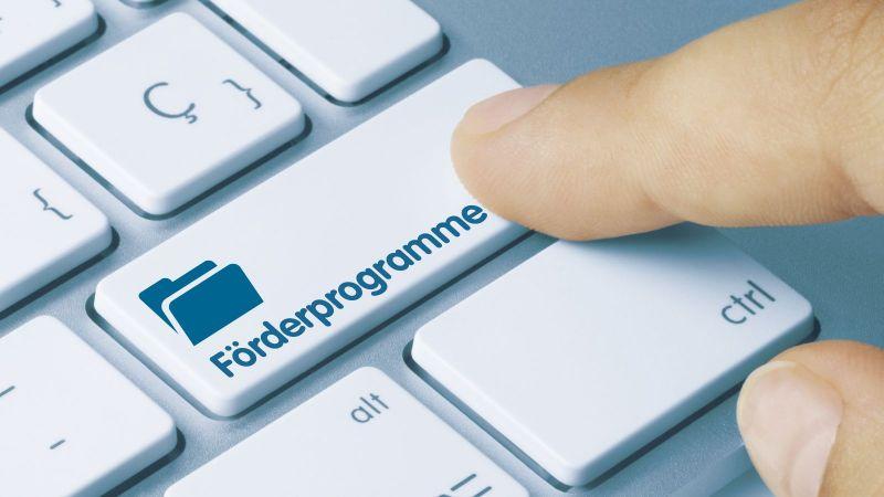 Tastatur mit der Beschriftung Förderprogramme auf einer Taste, die von einem Zeigefinger gedrückt wird.