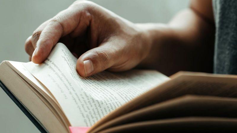 Das Bild zeigt ein aufgeschlagenes Buch, das durch eine Person gehalten wird.