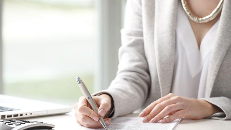 Das Bild zeigt eine Frau beim Lesen eines Dokuments.