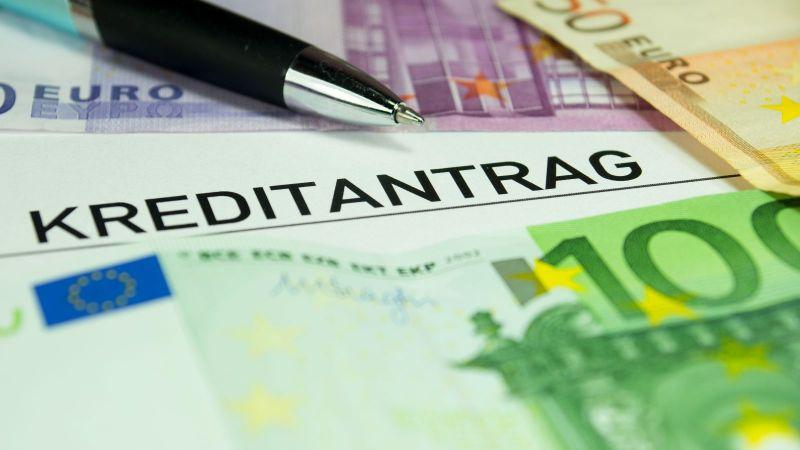 """Das Bild zeigt ein Dokument mit dem Titel """"Kreditantrag"""" auf dem mehrere Euro-Banknoten und ein Kuli liegen"""
