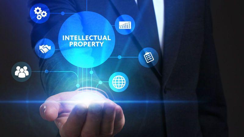 """Das Bild zeigt eine Hand, über der sich der Begriff """"Intellectual Property"""" in einem Kreis befindet, der wiederum mit kleineren Kreisen, die Symbole enthalten, verbunden ist."""