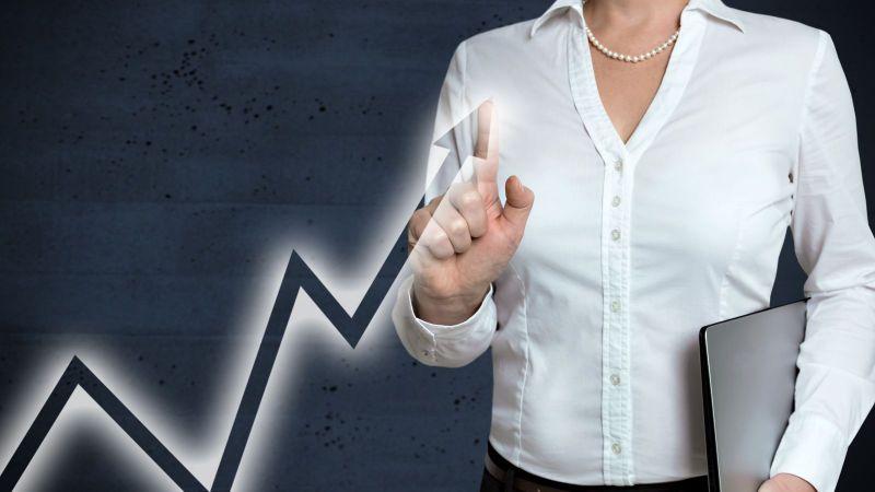 Das Bild zeigt eine Frau, die auf den nach-oben-zeigenden Pfeil einer ansteigenden Kurve zeigt.