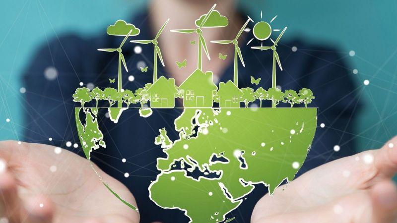 Eine Person hält eine halbe Erdkugel in den Händen auf der einige Windräder, Häuser, Bäume, Wolken und die Sonne in grün zu sehen sind