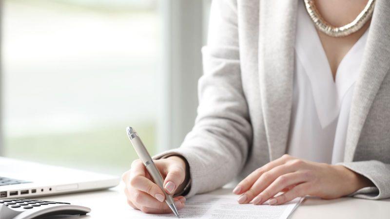 Das Bild zeigt eine Frau beim Unterzeichnen eines Dokumentes.