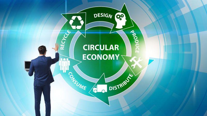 Diese Bild zeigt einen Mann im Anzug, der mit einem Laptop vor einer Wand steht, auf der ein grüner Kreis mit dem Wort