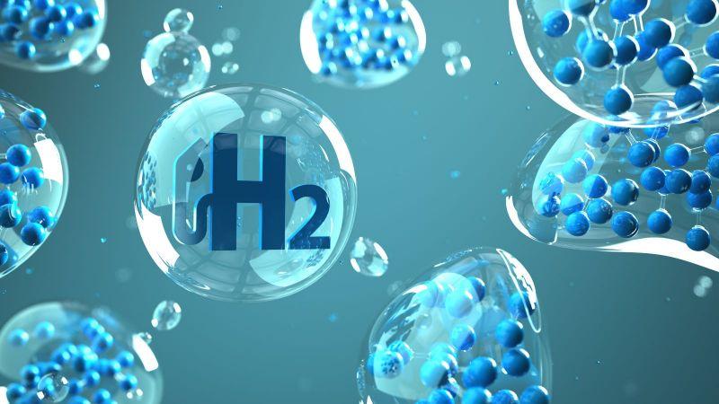 Das Bild zeigt Luftblasen mit verschiedenen Atomen und einer H2-Zapfanlage.