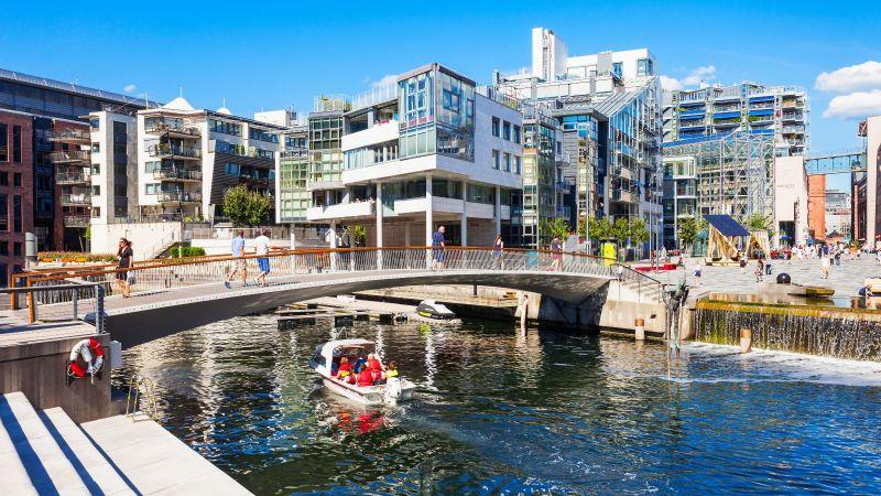 Das Bild zeigt einen Fluss in einer Stadt. Eine Brücke ist über dem Fluss zu sehen, auf der Menschen laufen.