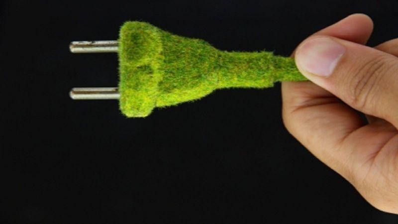 eine Hand hält einen grünen Stecker