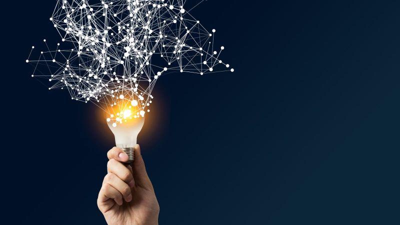 Eine Hand hält eine Glühbirne die leuchtet, aus der ein Netz mit verschiedenen Linien und Punkten herauskommt