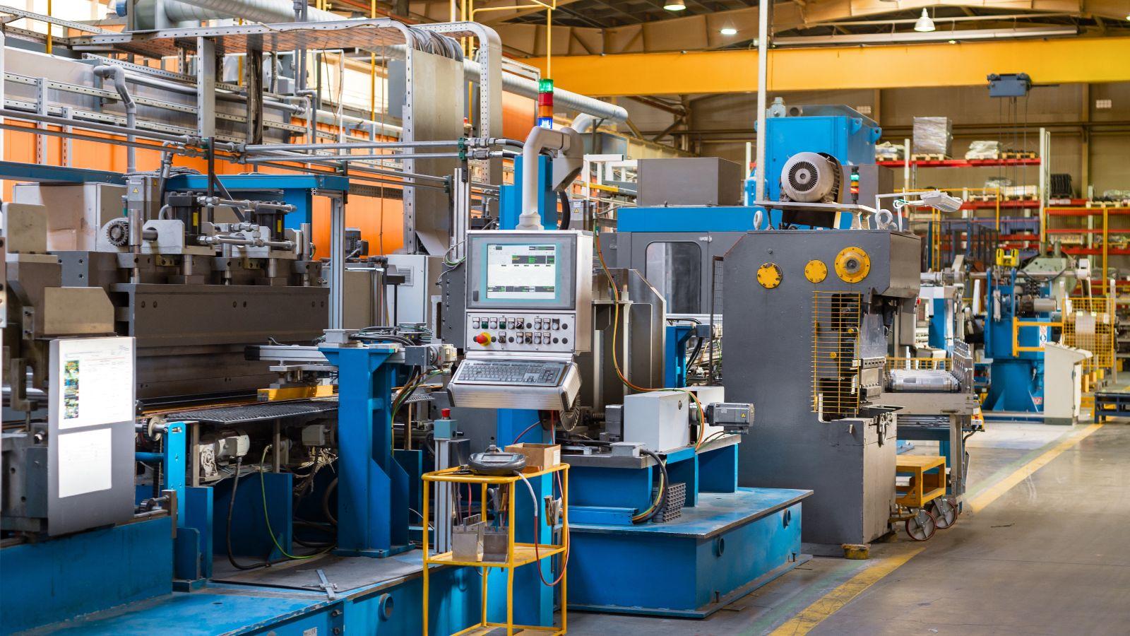 Dieses Bild zeigt eine Fabrikhalle, in der eine große Produktionsanlage für die Metallverarbeitung betriebsbereit steht. Im Zentrum des Bildes befindet sich das Steuerpult der Anlage.