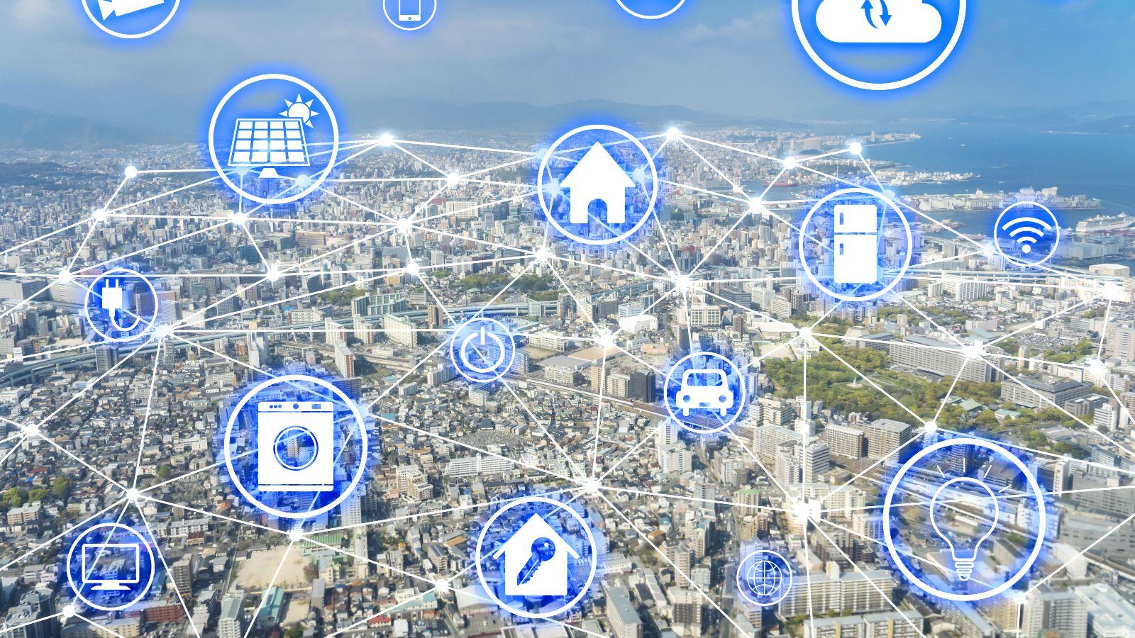 Diese Bild zeigt im Hintergrund eine Stadt. Im Vordergrund sind elektronische Symbole und Symbole von Haushalts- und Gebruachsgegenständen , wie zum Beispiel einem Haus, eine Solarpanel, einem Auto, einer Waschmaschine, einem Monitor, einer Glühbirne, einem Stecker, einer Überwachungskamera, einem WLAN-Zeichen, einem Smartphone, einer Wolke und einem Mikrofon dargestellt, die miteinander vernetzt sind,.